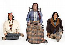 THREE LIFE-SIZE AMERICAN NATIVE FIGURES Two men and one woman. Beautifully carved wooden heads mounted to wood-frame bodies jointed...