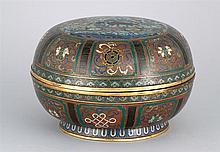 CLOISONNÉ ENAMEL COVERED BOX In circular form with lion and flower medallion surrounded by pahua motif on a rust-red ground. Diamete...