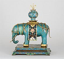 CLOISONNÉ ENAMEL ELEPHANT FIGURE In standing position, caparisoned with an urn and saddle blanket. All mounted on a rectangular base...