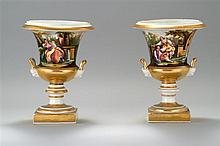 PAIR OF PARIS PORCELAIN URNS Decorated with scenes of courting couples and gilt highlighting. Figural head-form handles. Height 11.5
