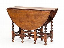 EARLY NEW ENGLAND DROP-LEAF GATE-LEG TABLE In maple. Three-board oval top over a single drawer. Bold block and turned legs joined by...