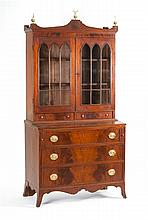 TWO-PART SECRETARY In mahogany and mahogany veneer with brass finials and eagle-form brass pulls. Upper section with two cathedral g...