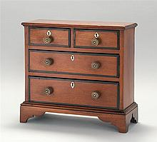 MINIATURE CHEST OF DRAWERS In mahogany with molded top. Two narrow drawers over two full-width graduated drawers, all with ebonized...