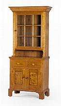 REPRODUCTION STEP-BACK CUPBOARD In tiger maple. Upper case with deeply molded cornice above a single glazed front door. Lower case w...