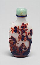 DOUBLE OVERLAY GLASS SNUFF BOTTLE In spade shape. With design of monkeys in a peach and pine tree landscape executed in blue and red...