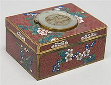 CLOISONNÉ ENAMEL COVERED BOX With jade-inlaid cover and floral design on a brick red ground. Length 4.1