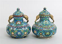 PAIR OF CLOISONNÉ ENAMEL COVERED JARS In squat ovoid form. Elephant's-head handles. Passionflower design on a blue ground. Height 13..