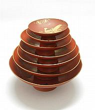 SET OF SEVEN GRADUATED RED AND GOLD LACQUER SAKE CUPS WITH STAND Decorated with figural scenes. Diameters 4.5