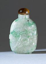 GREEN AND WHITE JADE SNUFF BOTTLE In elongated ovoid form with relief fruit and flower carving. Height 1.75