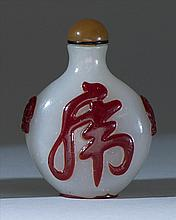 OVERLAY GLASS SNUFF BOTTLE In ovoid form with mask handles and stylized calligraphy in red on an opalescent ground. Height 2