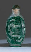OVERLAY GLASS SNUFF BOTTLE In elongated ovoid form with green dragon design on a clear ground. Height 2.8