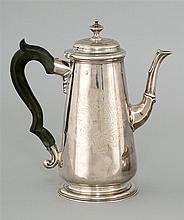 IRISH SILVER COFFEEPOT In tapering form with dome top, knop and ebony scroll handle. Maker's mark for John Hamilton of Dublin. Crest..
