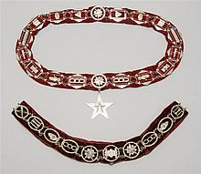 TWO ODD FELLOWS CEREMONIAL COLLARS Both with multiple silver-colored metal emblems mounted to red velvet. Lengths 16