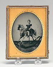 CASED PHOTOGRAPH Depicts a child on a rocking horse. Oval, length 4.5