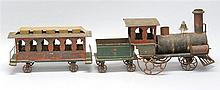 THREE-PIECE TIN TRAIN SET In red, green, yellow and black paint. Damage to locomotive. Length of passenger car 11