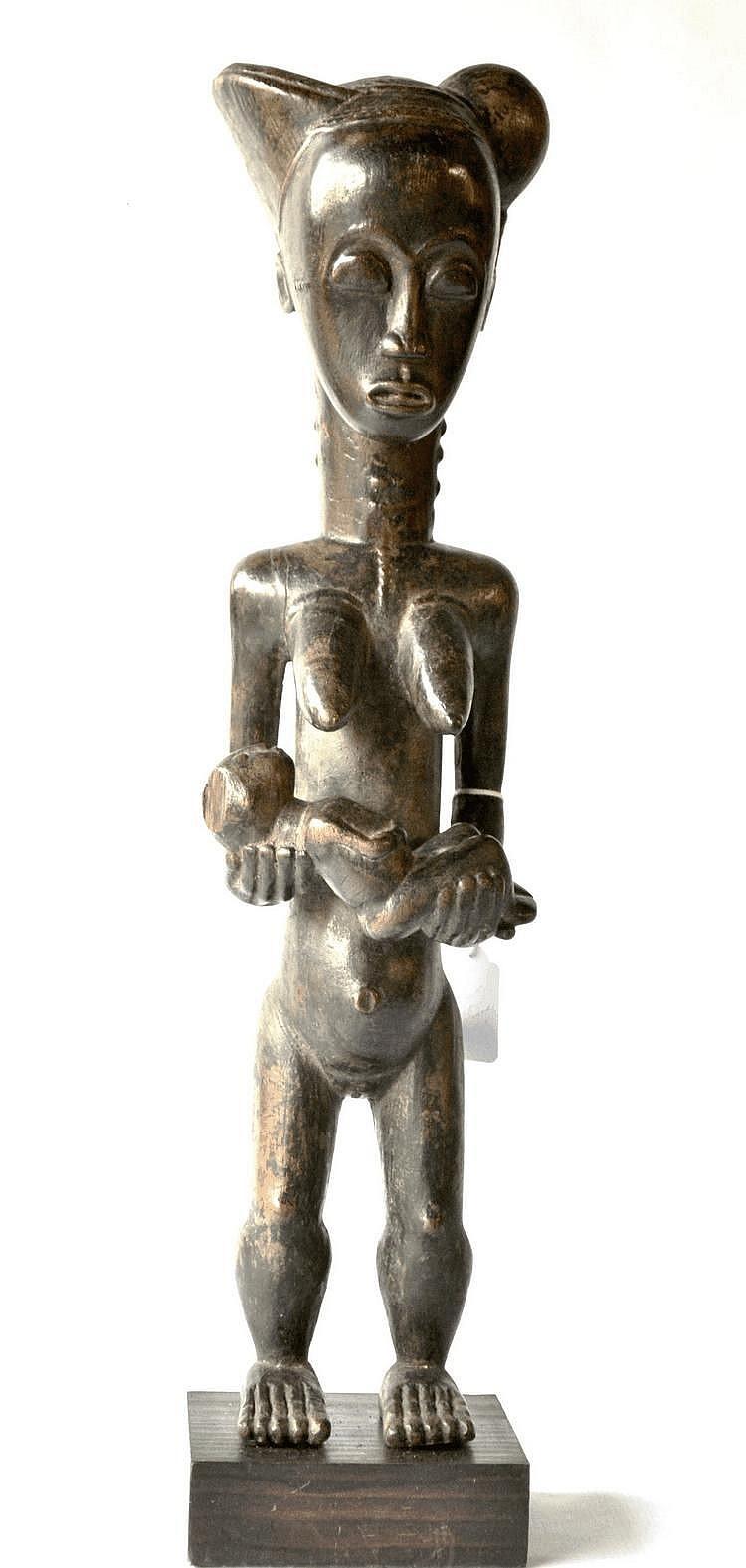 Côte d'Ivoire, BAOULE. Fort jolie statue féminine portant un enfant dans les bras. La coiffe royale et les yeux clos confèrent à cette pièce une dignité sobre et élégante. Le dos et le cou sont scarifiés de manière traditionnelle dans la statuaire
