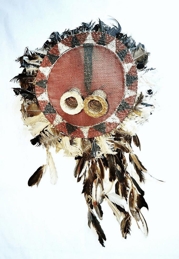 RDC,  Pende. Important masque de danse rond à plumes multicolores. Les yeux ronds confèrent à ce masque une expression toute particulière. Vannerie peinte, plumes.  37,5 cm sans les plumes