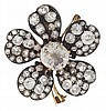 An antique diamond and silver-topped gold brooch, retailed by S.J. Phillips, London, designed as a flower, centering an old mine-cut di