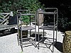 Pair of industrial three-tiered iron tables, circa 1900, The tubular painted iron frames supporting three square tiers, the top two wit