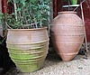 Two Mediterranean terracotta jardinieres, , Of ovoid form, the larger with pinched rope decoration, the shorter with raised ribbing.