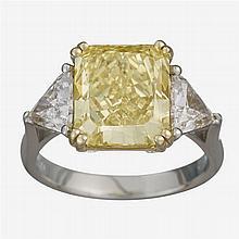 A fancy yellow diamond, diamond, platinum and eighteen karat gold ring,