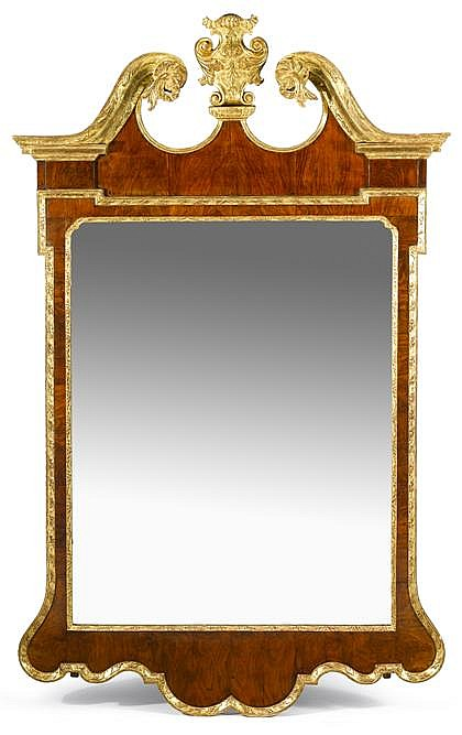 George II walnut and parcel gilt wall mirror, circa 1735, The acanthus carved broken pediment centered by acanthus scroll carved crest