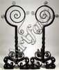 Large pair of black painted wrought iron andirons, , Each with spiral form top over twisted column, raised on scroll form base.