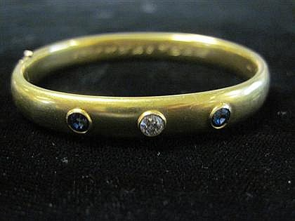 14 karat yellow gold, sapphire and diamond bangle, , Featuring a round cut diamond approximately .20 carats, framed on either side by a