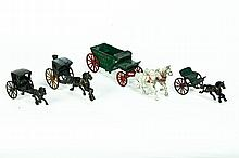 FOUR CAST IRON HORSE AND WAGONS.