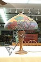 REVERSE PAINTED TABLE LAMP. Shade has a reverse painted forest and lake scene and rests on a foral embossed base. 22 1/4