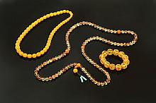 TWO CHINESE AMBER NECKLACES AND A BRACELET.
