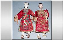 Pair of Chinese Wood and Gesso Dolls, lady and gentleman of wealth; each with roughly carved wooden torsos, upper arms and upper legs, the lower legs