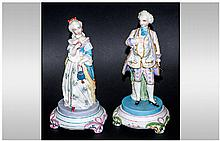 Pair of French Hand Painted Parian Figures of a lady and gentleman in 18thC courtly French dress, each standing on an integral circular, footed base;