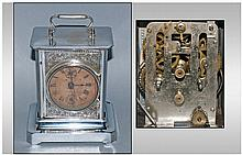 A Late 19th Century Silvered Metal Carriage Clock with a paper dial with two winding points to the back. Incorporated with a music box alarm system. W