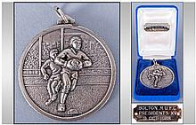 Bolton RUFC Presidents XV Silver Plated Medal, in original box, the medal showing a player running with the ball, pursued by another, in relief, again