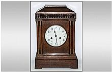 German / Austrian 19th Century Oak Cased Mantel Clock with Eight Day Striking and Chiming Movement on 4 Gongs. Porcelain White Dial and Black Numbers.