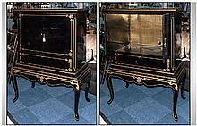 Black Lacquered Revolving Cabinet on shaped cabriole leg stand, decorated in gilt work, the two cupboards reveal a fretted brass work back. 58 inches