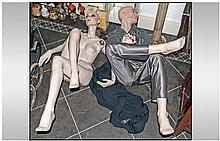 Two Mannequins comprising clothed man in seating