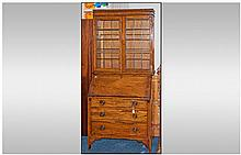 An Edwardian Oak leaded top Bureau Bookcase, with
