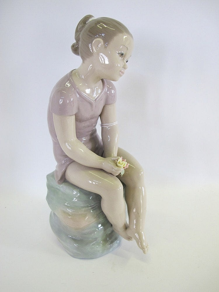 A large Nao porcelain figure of a girl seated on a
