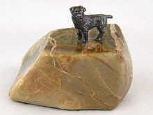 A silver model of terrier standing on a veined