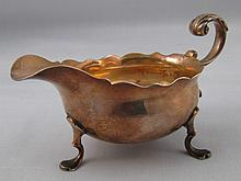 A George II silver sauceboat on three paw feet wit