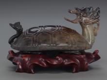 A CHINESE CARVED SMOKEY JADE FIGURE ON CARVED WOOD STAN