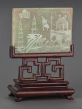 A CHINESE CARVED GREEN JADE PLAQUE ON A CARVED MAHOGANY