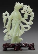 A CHINESE CARVED JADE GUANYIN FIGURE ON A CARVED WOOD B