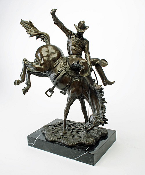 A BRONZE CAST OF A RODEO COWBOY RIDING A BUCKING BRONCO