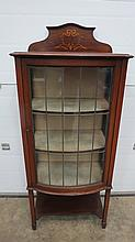 An Edwardian bow fronted glazed display case raised over square tapering legs united by solid undershelf.