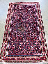 A Hamadan rug on red ground with pattern to centre and border, measuring 193 x 110cm.