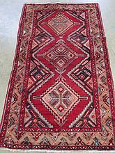 A Hamadan traditional rug, on red ground, diamond pattern to centre panel and patterned border, measuring 190 x 115cm.