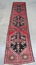 A Hamadan traditional style runner, on red ground, measuring 290 x 170cm.